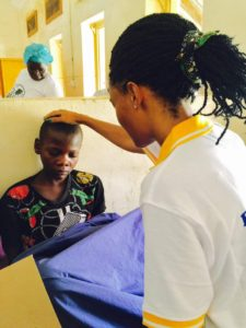 Sharon Okabe praying for sick children at Mbale Hospital