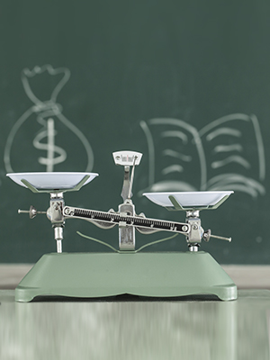 Drawing of dollar sign and the book on scales.