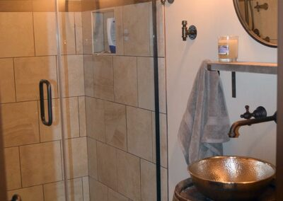 Bathroom with whiskey barrel sink and tiled shower
