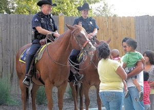 Mounted Denver Police Department officers greet neighbors and children at the West Colfax Cop Shop grand opening