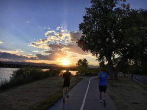 WeCAN Running Club running around Sloans Lake at sunset.