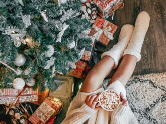 overhead shot of a christmas moment young woman in a cozy sweater sitting by a christmas tree woman t20 pR3p6j