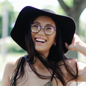 woman wearing glasses holding her hat