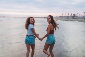 two girls running along a beach holding hands