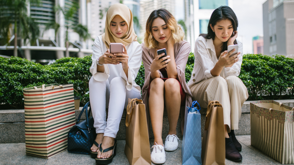 three-women-sitting-looking-at-their-phones-with-shopping-bags