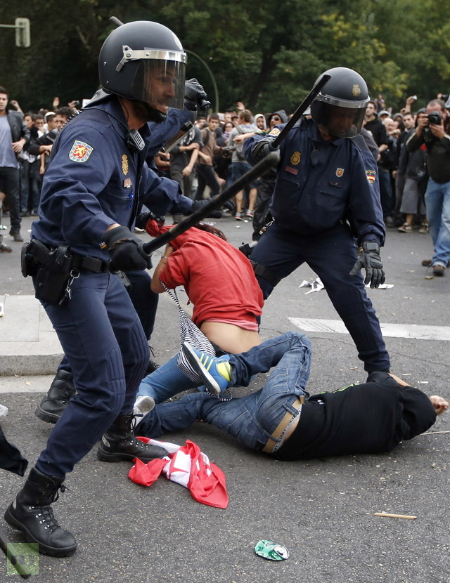 Police charge at demonstrators outside the the Spanish parliament in Madrid