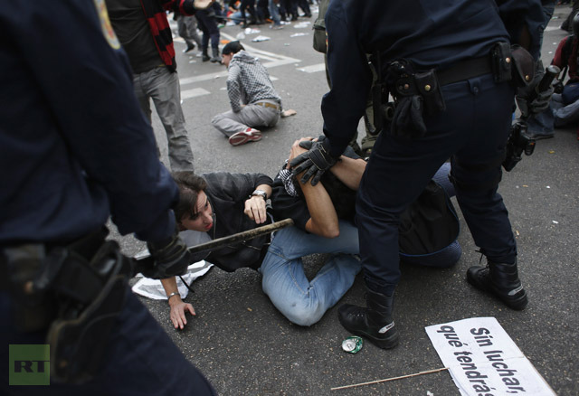 Spanish riot police push demonstrators onto floor outside parliament in Madrid