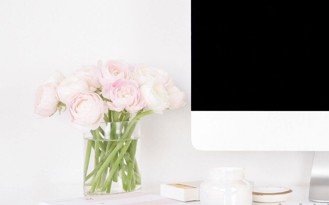 blog post ideas for your business website with a black computer screen and pink flowers