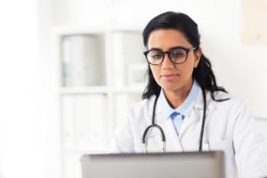 telemedicine services nurse computer stethoscope white robe laptop glasses