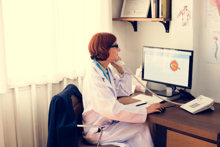 telemedicine software doctor on phone calls software telephone online woman glasses computer