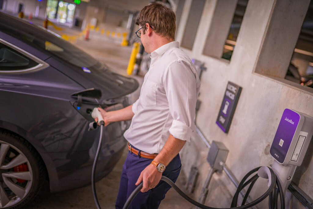 Man plugs his electric vehicle into a EV charger in a parkade