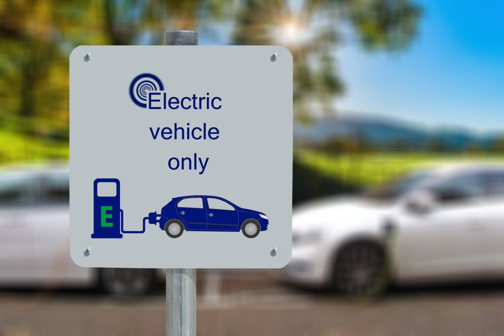 A sign in a parking lot indicating the spot is for electric vehicles and EV charging only