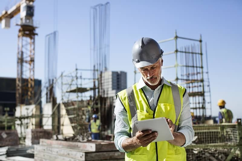 Architect using digital tablet at site-cm