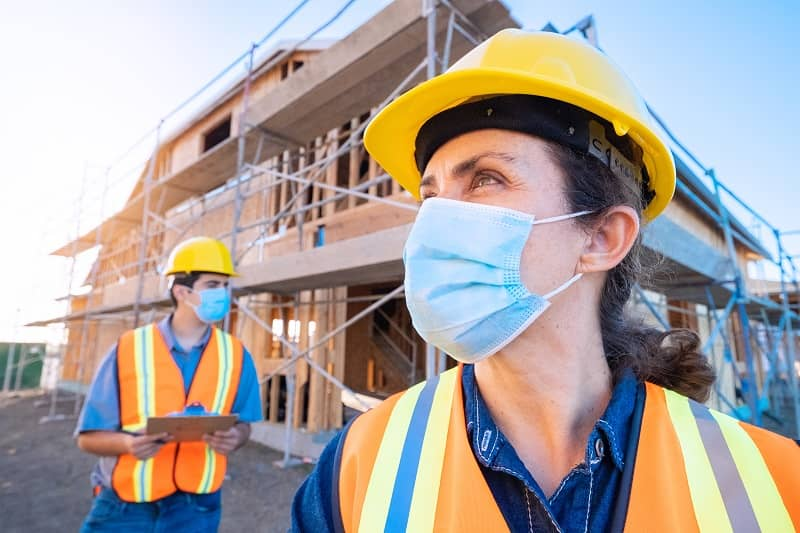 Mature female construction worker looking at the camera wearing a protective face mask -cm