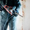 worker using pneumatic hammer drill to cut the wall concrete brick, close up-cm