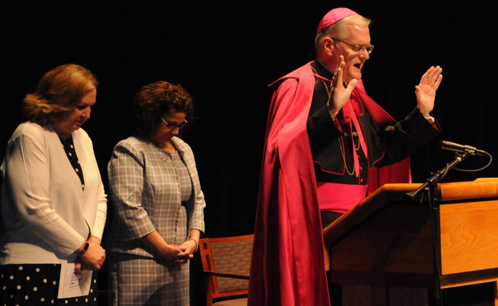 Bishop Joseph M. Siegel, right, blesses Reitz Memorial High School Class of 2019 on May 19, as Assistant Principal Lisa Popham, left, and Principal Sally Sternberg bow their heads.