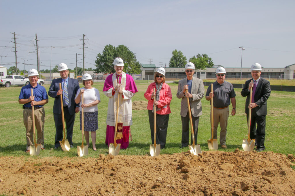 Preparing to turn the first shovels of dirt on the site of Catholic Charities of the Diocese of Evansville's future home are Dan Ritter, left, Catholic Charities Building Committee chairperson; Mike Vogel, President of the Catholic Charities Board of Advisors; Catholic Charities Executive Director Sharon Burns; Bishop Joseph M. Siegel; Charline and Mike Buente of Buente-Buente Architects PC; Dan Jones of Danco Construction, Inc.; and Diocesan Chancellor and Chief Operating Officer Tim McGuire.