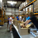 A Mission Evansville crew packs boxes for Tri-State Food Bank's low-income senior citizen meal program, which serves over 1,200 people in need in Indiana and Illinois once a month.