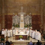 Father Raymond Brenner, center, stands at the altar with deacons Levi Schnellenberger, left, and Martin Estrada, at the beginning of the Eucharistic Prayer. At the back left are his great nephews Jonathan Brenner, left, and Timothy Brenner, altar servers for the May 19 Mass. Standing on the altar with them are concelebrants Fathers Ron Kreilein, left, Eugene Schmitt, Bill Traylor, Joe Ziliak, Christopher Droste, Tony Ernst, Dave Martin, Lowell Will, John Boeglin, John Brosmer, Pat Gaza, Anthony Govind, Crispine Adongo, Jim Koressel, Steve Lintzenich, Tim Tenbarge, John Schipp and Joseph Erbacher. At the far right is Director of St. Joseph Youth Choir Mary Burke, who served as cantor.