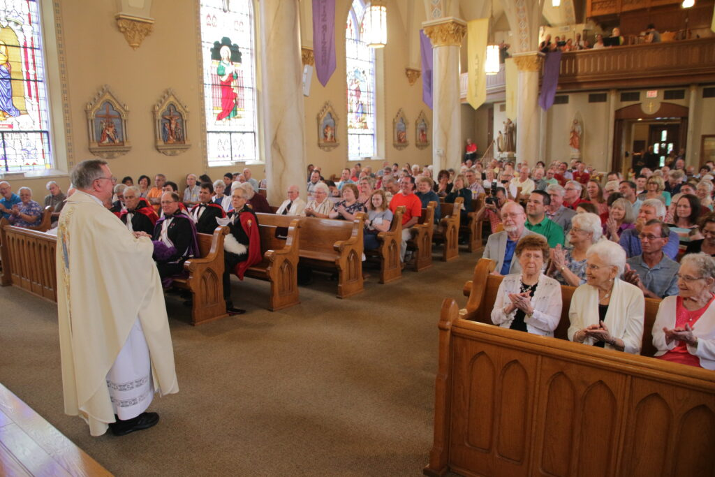Father Jim Koressel, left, receives an ovation from people who travelled from across the Diocese of Evansville for his June 9 Mass of Thanksgiving at St. Peter Parish in Montgomery. Father Koressel, who retires from pastoral ministry later this month, was ordained a priest of the Diocese of Evansville on May 17, 1969.