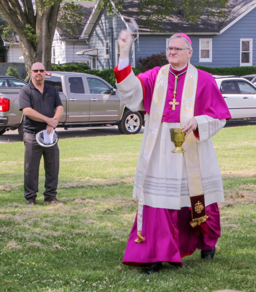 Bishop Siegel sprinkles holy water around the grounds of the future home of Catholic Charities during the June 3 groundbreaking ceremony.