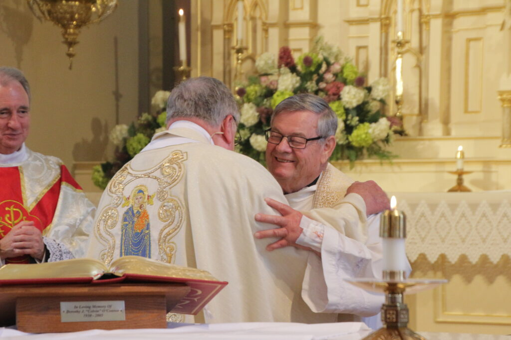 Father Koressel, left, shares the sign of peace with his classmate, Father Ray Brenner. Father Brenner, who also retires from pastoral ministry this month, is pastor of St. Joseph Parish in Jasper and Dean of the Diocese of Evansville East Deanery.