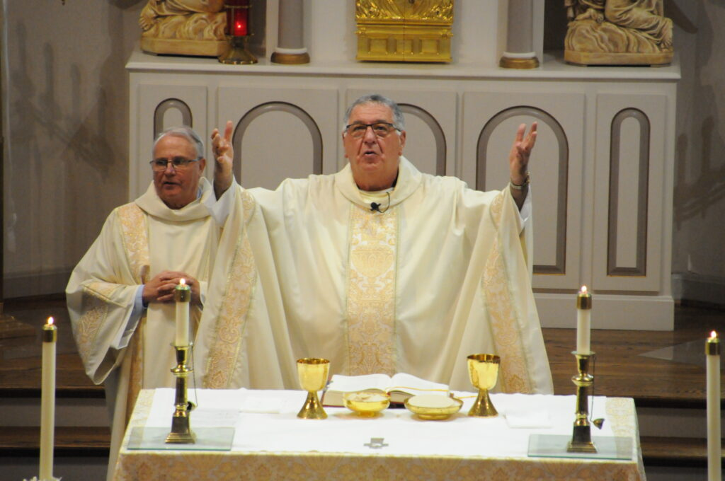 Father Sauer prays the Eucharistic Prayer during his final Mass before retirement at St. Matthew Parish on June 23, with Deacon Tom Evans assisting.