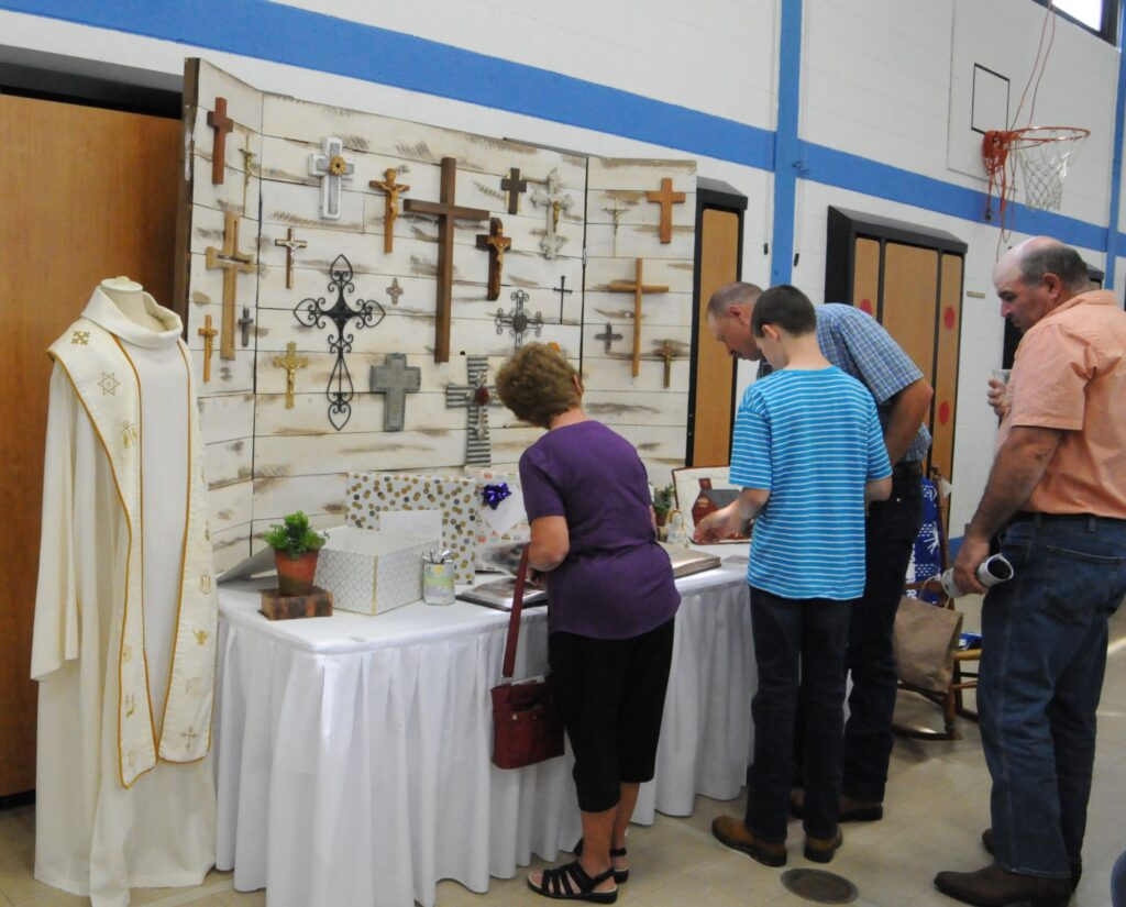 Nearly 400 parishioners and community members celebrated Father Sauer at an open house luncheon on June 23 in St. Matthew's gymnasium. Parishioners check out photo albums and other gifts that were given to Father Sauer.