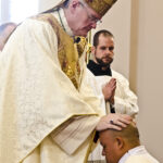 Photo by Kevin J. Kilmer The Most Reverend Joseph M. Siegel, Bishop of Evansville, lays his hands on Deacon Juan Ramirez as he ordains him Saturday, in St. Philip Church, Mount Vernon, Ind., during the Rite of Ordination.