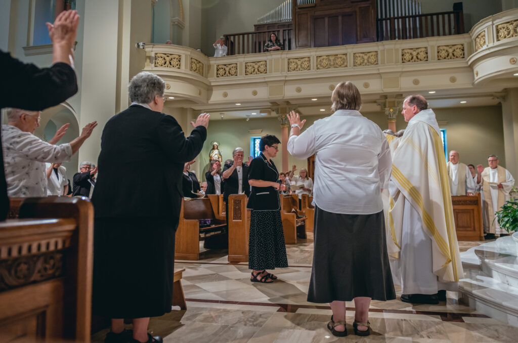 Benedictine Rt. Rev. Kurt Stasiak, right, leads a prayer of blessing for Benedictine Sister Anita Louise Lowe as she is installed as the 14th prioress during a July 13 Mass at Monastery Immaculate Conception in Ferdinand. At right in the background are Father Joseph Ziliak and Father Ray Brenner, retired priests of the Diocese of Evansville. Father Bernie Lutz, retired priest of the diocese, also attended but is not pictured.