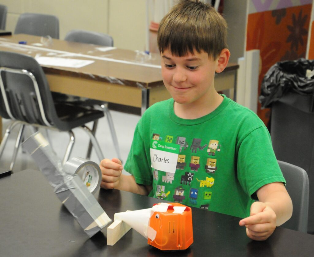 Corpus Christi fourth-grader Charles Baker tests the bulldozer robot he created to see if it will knock over a tower he built.