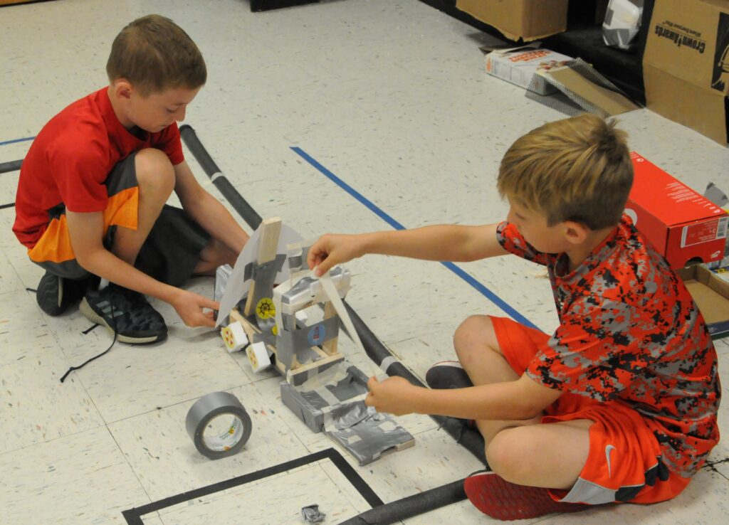 Good Shepherd Catholic School fourth-graders John Pietruszkiewicz and Gus Theby build a ship during Camp Invention: Supercharged.