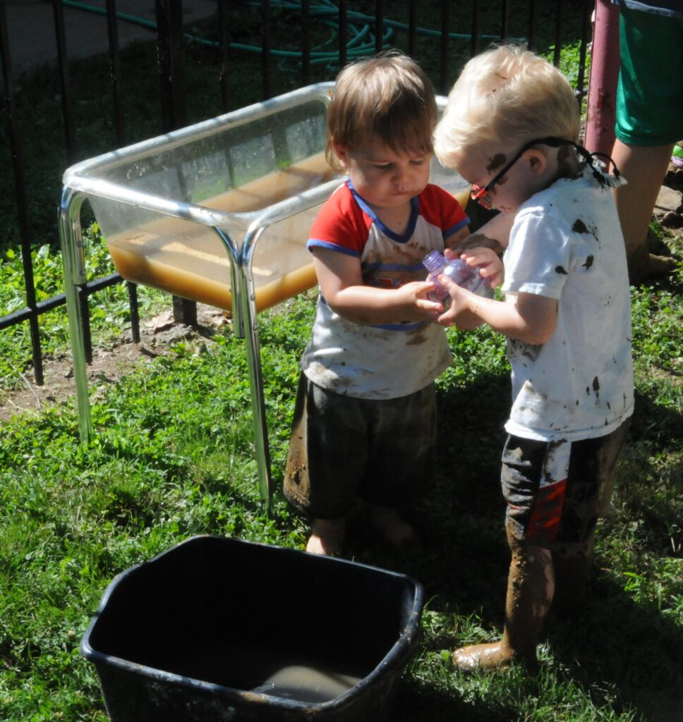 Tristan Clapp, left, and Phillip Hyndman play with muddy water during St. Vincent Early Learning Center's celebration of International Mud Day.