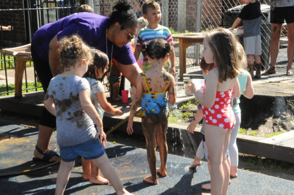 Alissa Mwenelupembe, St. Vincent Early Learning Center director of early learning, hoses mud off of some kids during the center's celebration of International Mud Day on June 28.