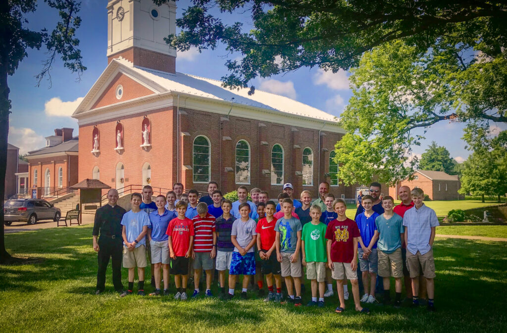 With the Minor Basilica of St. Francis Xavier in Vincennes behind them, Father Tyer Tenbarge, left, associate director of vocations for the Diocese of Evansville, stands with youngsters who attend Savio Nights at the Father Deydier House of Discernment with some of their fathers, who made the June 26 pilgrimage to Vincennes, and Diocese of Evansville seminarians Tyler Underhill and Keith Hart. Submitted photo courtesy of Father Tyler Tenbarge