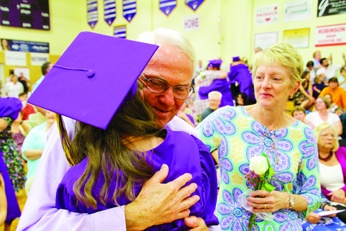 Rivet High School Class of 2019 President Savannah Cook hugs her father Joe, left, as her mother Janet looks on. Savannah joined her classmates in presenting flowers and hugs of gratitude to their parents during Commencement. Janet is holding the flower Savannah gave her with a huge hug.