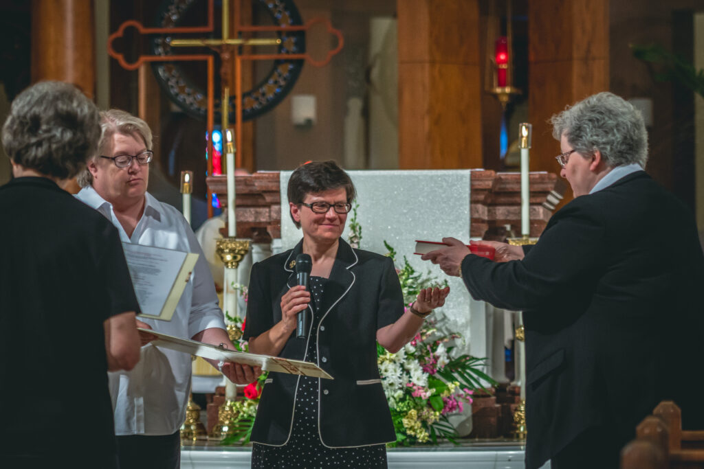 Benedictine Sister Barbara Lynn Schmitz, right, presents Sister Anita Louise Lowe with the Book of the Gospels during her installation as prioress — replacing Sister Barbara Lynn — during a July 13 Mass at Monastery Immaculate Conception.