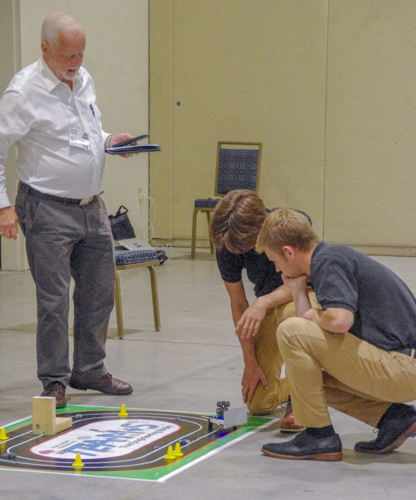 A TEAMS judge, left, watches Rivet students James Hancock and Noah Donovan during the June 30 Design and Build Competition. Submitted photo