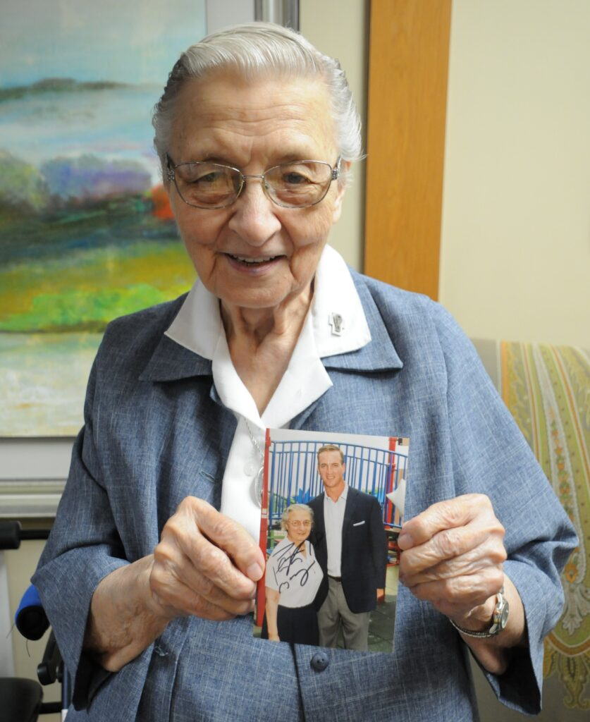 Daughter of Charity Sister Mary John Tintea holds an old photograph of herself with Former NFL quarterback Peyton Manning, which he autographed after the press conference.