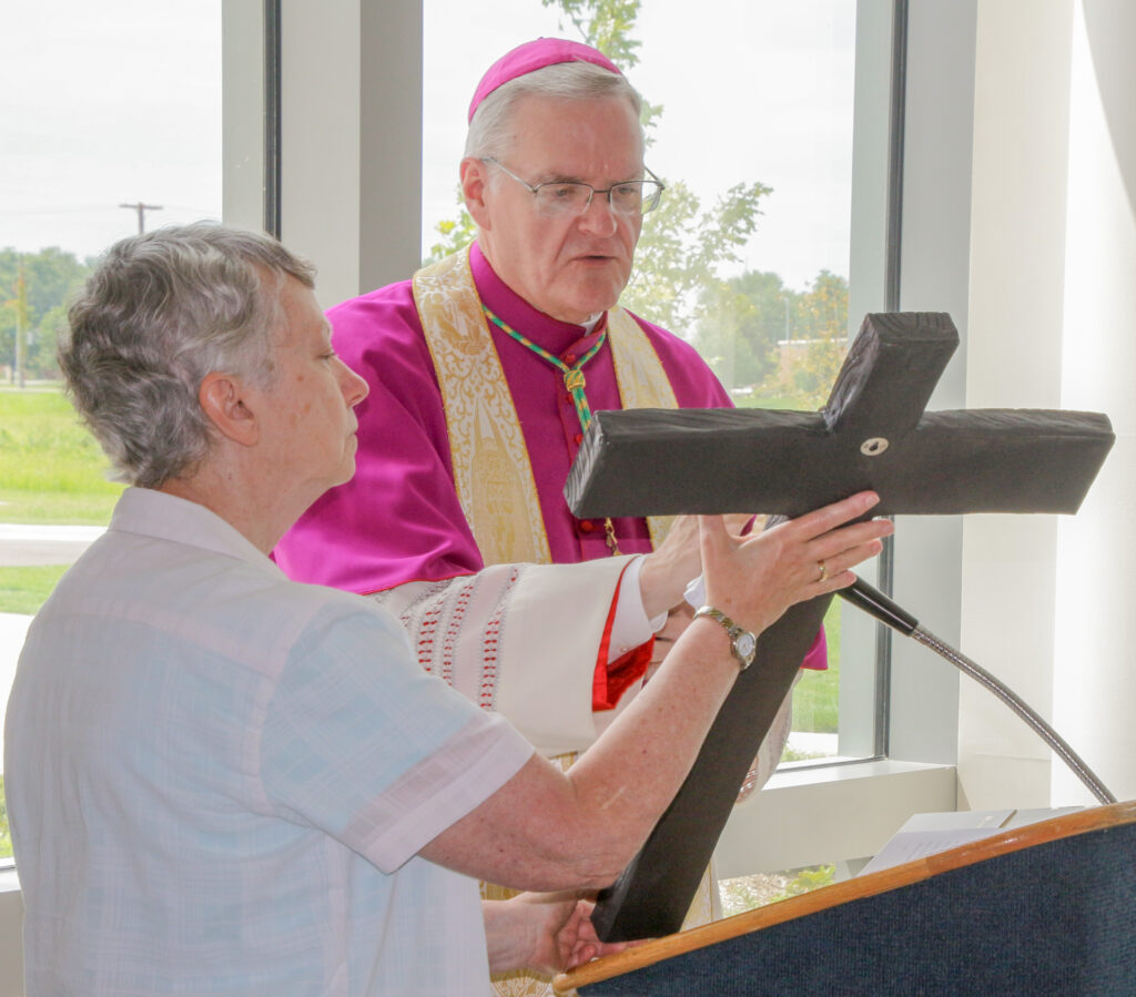 Bishop Siegel blesses the crucifix for the hospital's main entry area, which Sister Jane is holding.