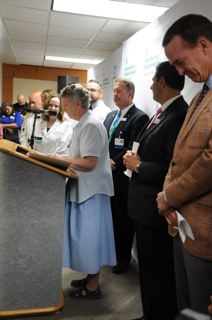 Franciscan Sister Jane McConnell, standing at podium, head of mission integration for St. Vincent Evansville, led the group in prayer on Aug. 14 before the news conference.