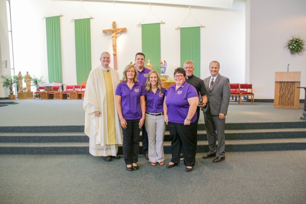Holy Trinity School in Jasper received the Catholic Educator Innovator Award after the Back-to-School Mass on Aug. 2 at Good Shepherd Parish. Pictured are Charmaine Oxford, front row left, teacher; Jenna Seng, Holy Trinity Central Campus principal; Benedictine Sister Becky Mathauer, teacher; Bishop Joseph M. Siegel, back row left; Jon Temple, Holy Trinity East Campus principal; Father Gary Kaiser, pastor of Precious Blood Parish in Jasper; and Dr. Daryl Hagan, diocesan schools superintendent.