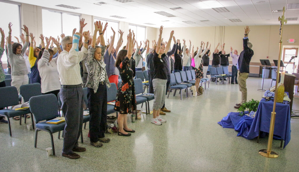 "Dr. Tim Hogan, right, leads Formation Day attendees through a breathing exercise designed to have a calming effect. ""We all have to be open to receiving God,"" he said."