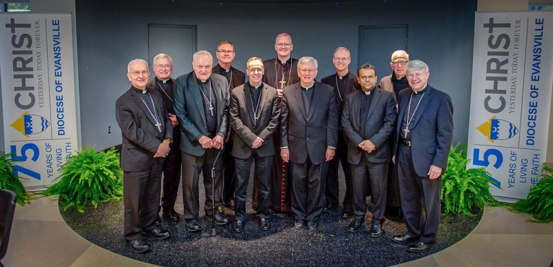 Bishop Siegel, center, stands with honored guests during the luncheon that preceded Mass. Shown are Bishop-Emeritus Dale Melczek, left, of the Gary, Bishop David Malloy of Rockford, Bishoop-Emeritus Gerald A. Gettelfinger, Bishop Timothy Doherty of Lafayette, Archbishop Charles C. Thompson of Indianapolis, Bishop David Ricken of Green Bay, Archbishop Paul Etienne of Seattle, Monsignor Dennis Kuruppassery of the Apostolic Nunciature, former Benedictine Archabbot Lambert Reilly of Saint Meinrad and Bishop Daniel Conlon of Joliet. Not pictured are Bishop William Medley of Owensboro and current Saint Meinrad Archabbot Kurt Stasiak, who also concelebrated Mass. The Message photo by Jay Hamlin