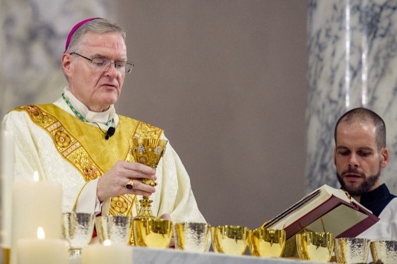 Bishop Siegel elevates the Reitz Chalice during the dedication Mass. He is wearing an episcopal ring that was worn by Bishop Henry Grimmelsman, the first bishop of Evansville.  The Message photo by Jay Hamlin
