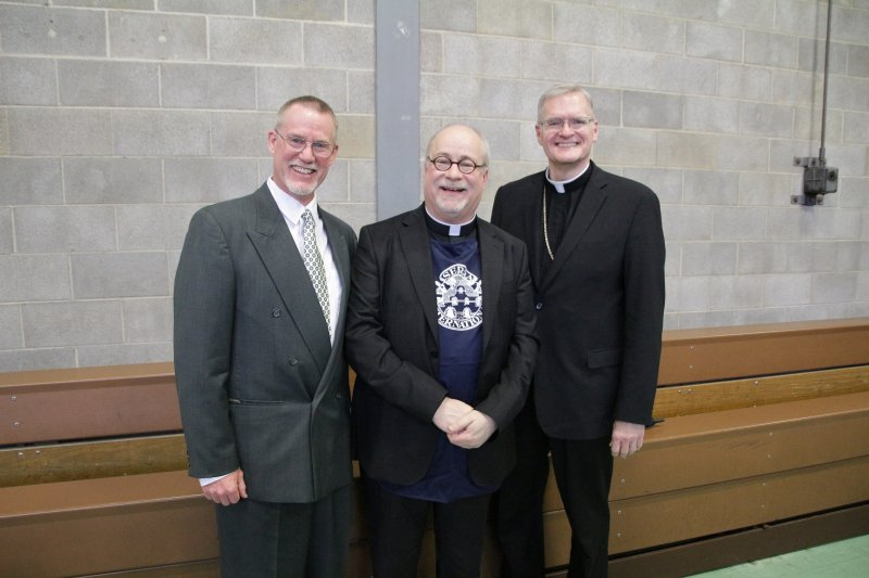 Benedictine Father Denis Robinson of Saint Meinrad wears the Serra Club apron he received from club president John East, left. Bishop Joseph M. Siegel joined them for the photo. The Message photo by Tim Lilley