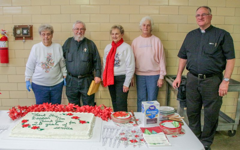 Deacon Lambert, second from left, prepares to cut the cake made in his honor. Joining him are WESK volunteers and Father Jack Durchholz, pastor of St. Clement Parish. The Message photo by Tim Lilley
