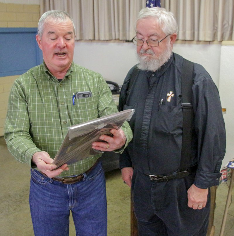 St. Clement parishioner and Knight of Columbus Dennis McVey, left, reads the inscription on the plaque Deacon Thomas Lambert received in recognition of his service to the community through WESK. The Message photo by Tim Lilley