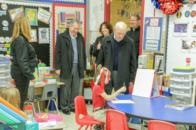 Koch Enterprises, Inc. Chairman Bob Koch listens to Holy Redeemer second-grader Alivia Ashby describe her practice in cursive writing. Behind them, First-Grade Teacher Lisa McCall, left, visits with Koch Enterprises, Inc. Vice-Chairman Jim Meuhlbauer, Holy Redeemer Principal Andrea Dickel and Holy Redeemer Pastor Father Jason Gries. The Message photo by Tim Lilley