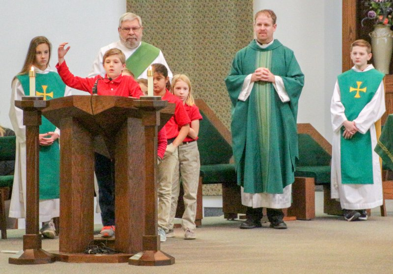 Holy Redeemer second-grader Hayes McCure offers a petition during a Jan. 30 School Mass at the parish. He and some of his classmates offered petitions.. The Message photo by Tim Lilley
